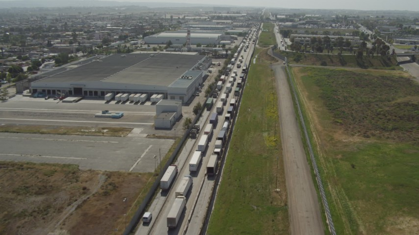 4K aerial video of a line of trucks by warehouses, US/Mexico Border, Tijuana Aerial Stock Footage | DCA08_083