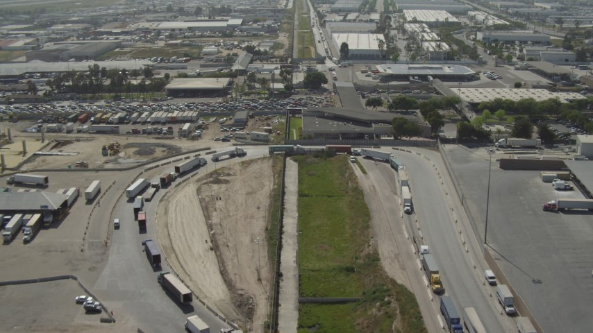 4K stock footage aerial video of approaching big rigs crossing the US/Mexico Border, Tijuana Aerial Stock Footage | DCA08_086