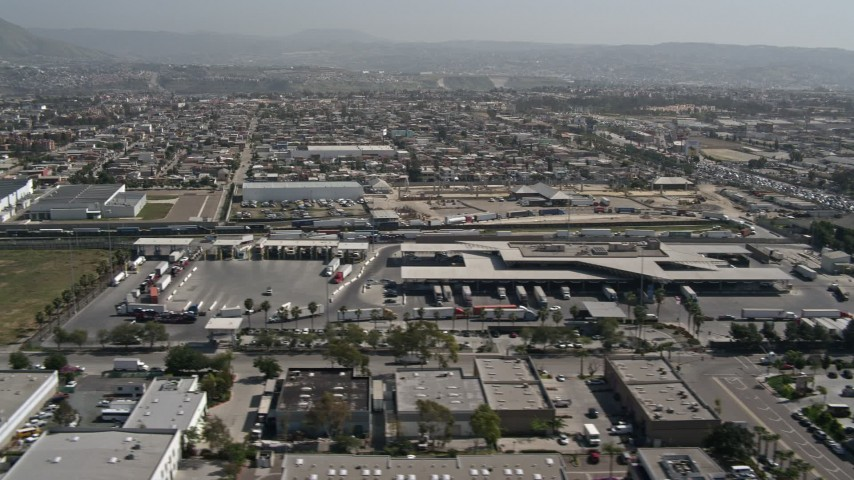 4K aerial video of flying by the US/Mexico Border checkpoint in Otay Mesa, California Aerial Stock Footage | DCA08_093