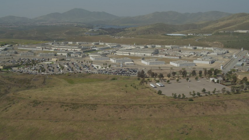 4K stock footage aerial video tilt from hill to reveal prison, Otay Mesa, California Aerial Stock Footage | DCA08_102