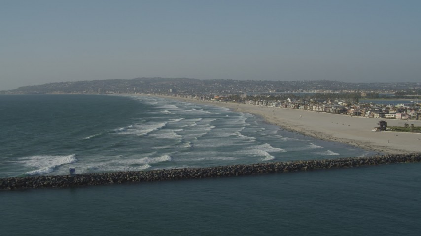 4K stock footage aerial video fly over ocean waves to approach a beach and beachfront homes, Mission Beach, California Aerial Stock Footage   DCA08_229