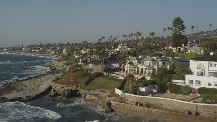 4K stock footage aerial video tilt from the ocean to reveal oceanfront mansions, La Jolla, California Aerial Stock Footage | DCA08_241