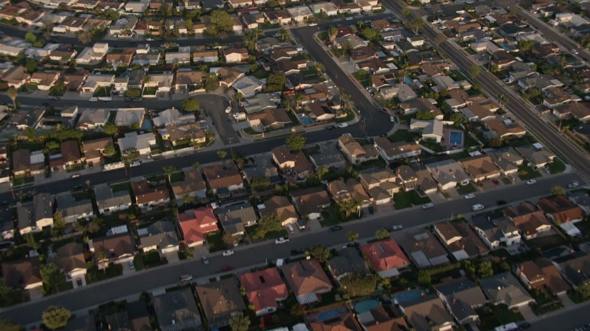 4K aerial video of a reverse view of tract homes in the suburbs, Clairemont Mesa East, California, Sunset Aerial Stock Footage DCA08_271