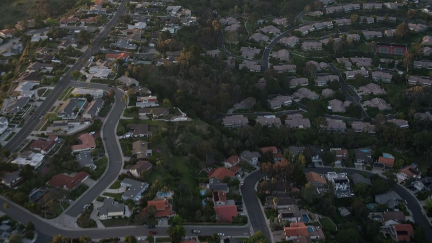4K stock footage aerial video of a reverse view of tract homes and reveal park, La Jolla, California, Sunset Aerial Stock Footage | DCA08_282