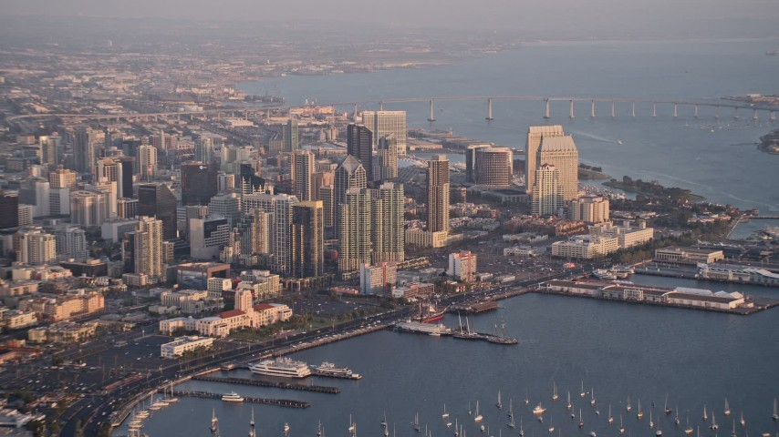 4K stock footage aerial video of a high altitude approach to skyscrapers, pan across Downtown San Diego, California, Sunset Aerial Stock Footage | DCA08_291