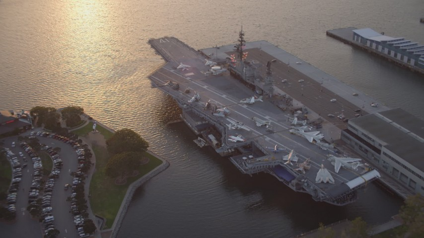 4K stock footage aerial video orbit of the USS Midway, a Naval aircraft carrier, Downtown San Diego, California, Sunset Aerial Stock Footage DCA08_305