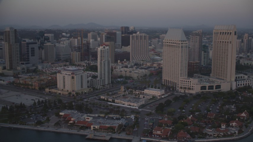 4K stock footage aerial video tilt from seafood company to reveal skyscrapers and hotels in Downtown San Diego, California, Sunset Aerial Stock Footage | DCA08_321