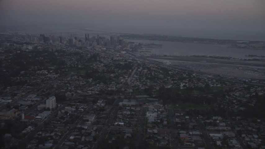 4K aerial video of flying by Downtown San Diego, and San Diego International Airport, California, twilight Aerial Stock Footage | DCA08_331