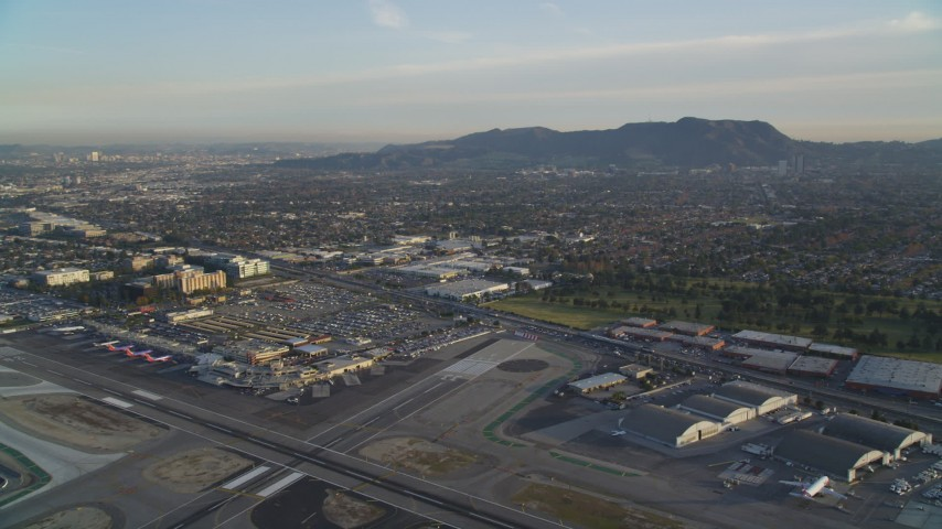 5K stock footage aerial video fly over runways at Burbank Airport and tilt to terminals at sunset, California Aerial Stock Footage | DCLA_002