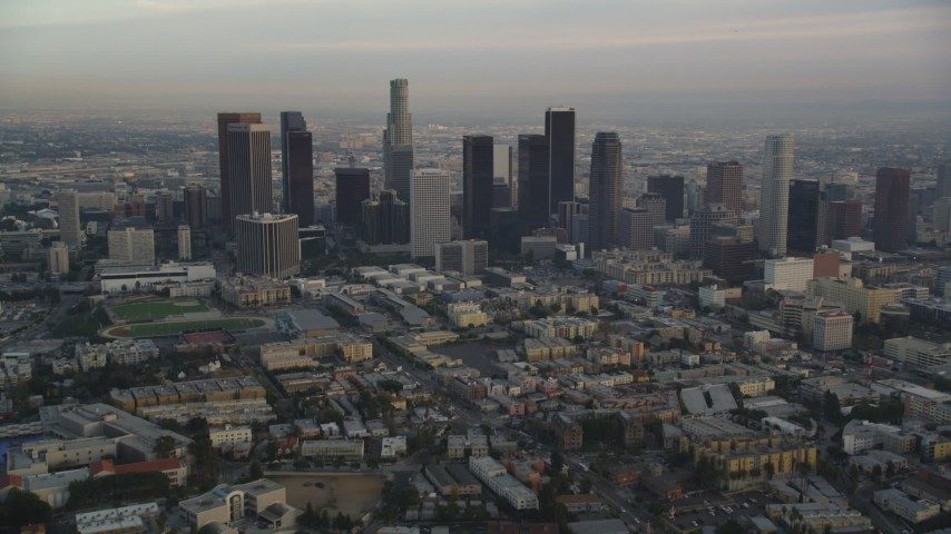 5K stock footage aerial video tilt from Hollywood streets to reveal and approach Downtown Los Angeles skyline at sunset, California Aerial Stock Footage | DCLA_015
