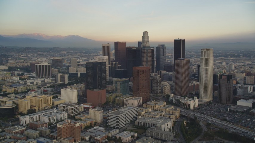 Tilt from Office Buildings to Reveal and Approach Downtown Los Angeles at Sunset Aerial Stock Footage | DCLA_024