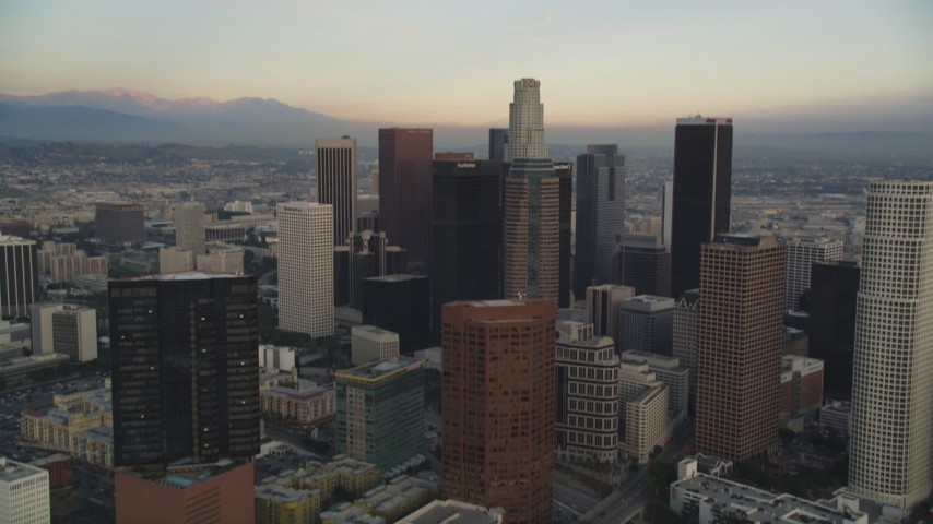 5K stock footage aerial video tilt from city streets to reveal and approach Downtown Los Angeles at sunset, California Aerial Stock Footage | DCLA_025