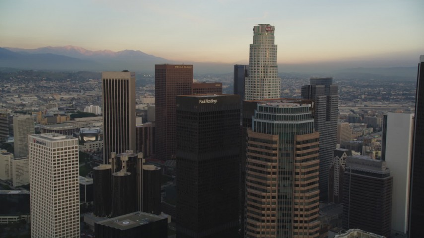 Tilt from Busy Street to Reveal and Approach Downtown Los Angeles, California Skyscrapers at Sunset Aerial Stock Footage | DCLA_026