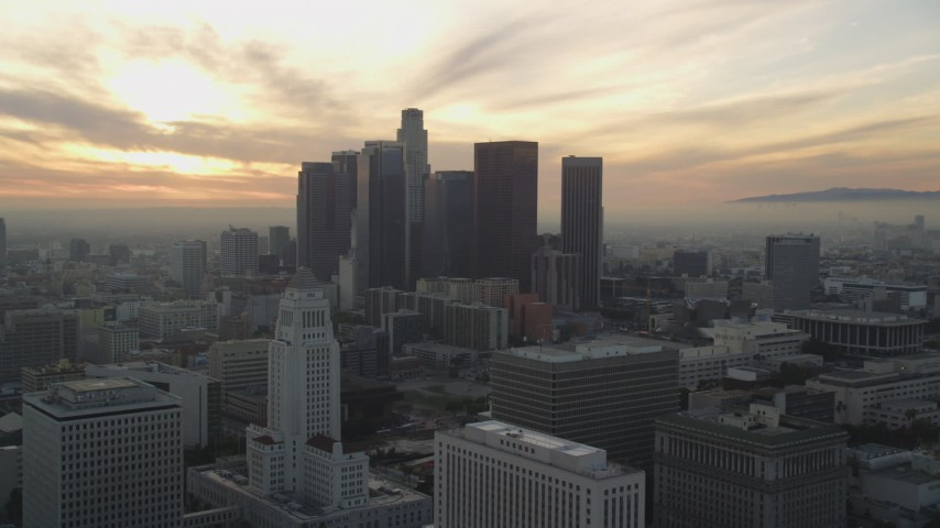 5K stock footage aerial video reverse view of City Hall and Downtown Los Angeles skyline at sunset, California Aerial Stock Footage | DCLA_031