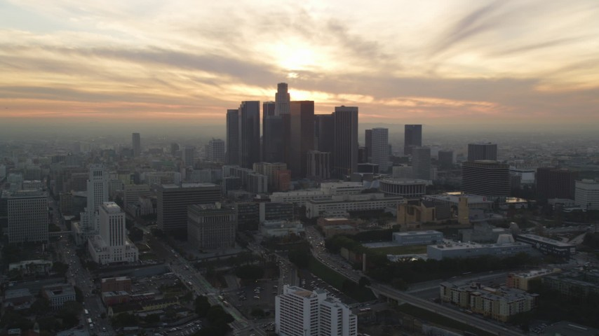 5K stock footage aerial video of Downtown Los Angeles skyline with setting sun in the clouds, California Aerial Stock Footage | DCLA_034