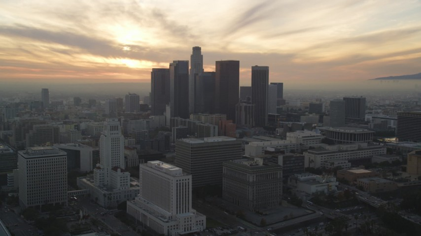Approach Downtown Los Angeles Skyline with Setting Sun behind Clouds Aerial Stock Footage | DCLA_035