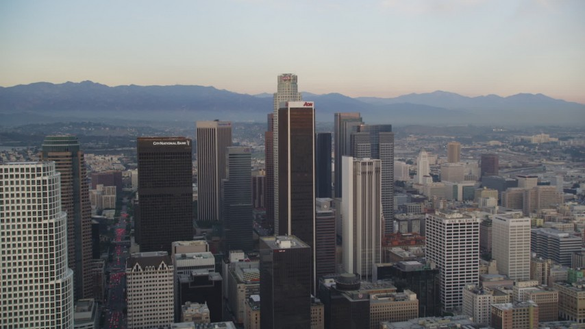 5K stock footage aerial video tilt from busy streets, reveal and approach skyscrapers in Downtown Los Angeles at twilight, California Aerial Stock Footage | DCLA_042
