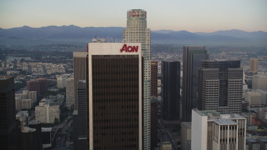 5K stock footage aerial video tilt from high-rises, reveal and approach Aon Center and US Bank Tower at twilight in Downtown Los Angeles, California Aerial Stock Footage | DCLA_043