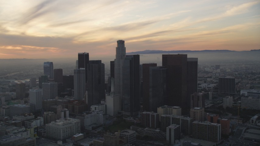 5K stock footage aerial video approach Downtown Los Angeles with sunset-lit clouds overhead, California Aerial Stock Footage | DCLA_047