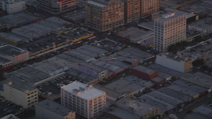Track Police Helicopter Flying Over Downtown Los Angeles, California at twilight Aerial Stock Footage | DCLA_056