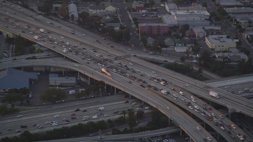 Track Police Helicopter over Freeway Gridlock at twilight in Downtown Los Angeles, California Aerial Stock Footage | DCLA_059