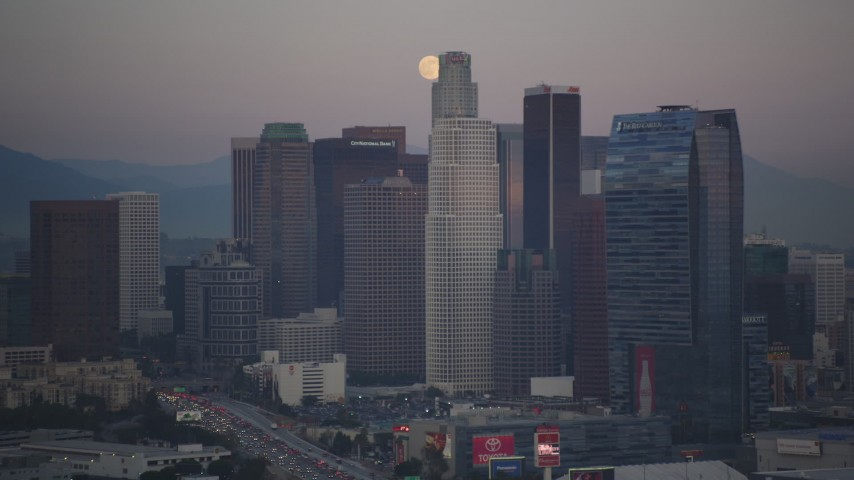 5K stock footage aerial video of a full moon behind Downtown Los Angeles skyscrapers at twilight, California Aerial Stock Footage | DCLA_065
