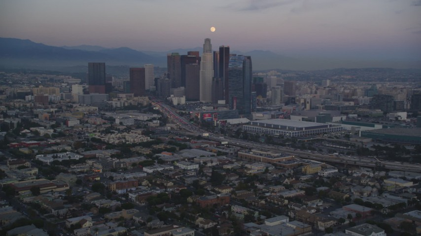 5K stock footage aerial video tilt from Pico-Union streets to reveal Downtown Los Angeles skyline and full moon at twilight, California Aerial Stock Footage | DCLA_070
