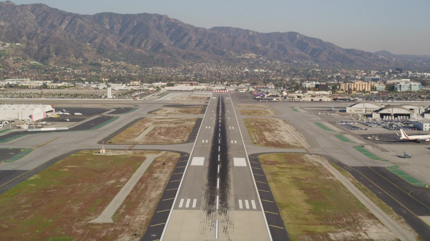 5K stock footage aerial video tilt to reveal and approach runway at Burbank Airport, California Aerial Stock Footage | DCLA_103