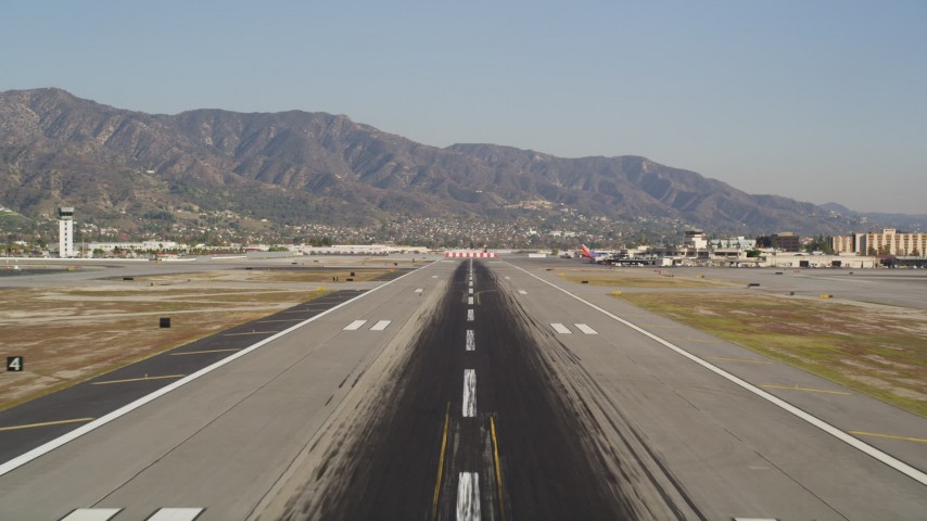 5K stock footage aerial video tilt and fly over the runway at Bob Hope International Airport in Burbank, California Aerial Stock Footage | DCLA_104