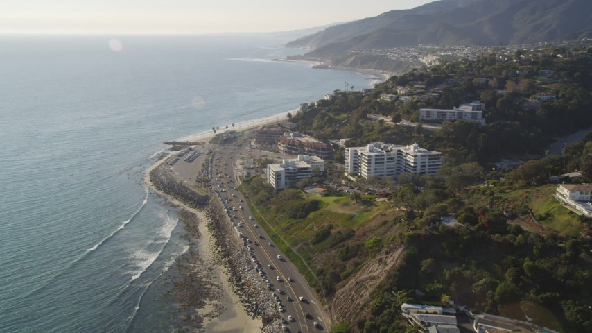 5K stock footage aerial video follow Highway 1 to approach condos in Pacific Palisades, California Aerial Stock Footage | DCLA_135