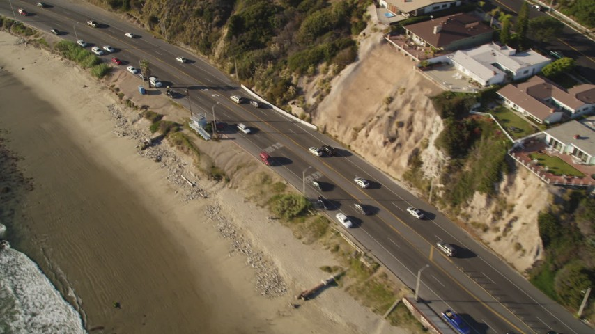 Tilt from Highway 1 to Reveal Neighborhood  on Cliff in Malibu, California Aerial Stock Footage | DCLA_138