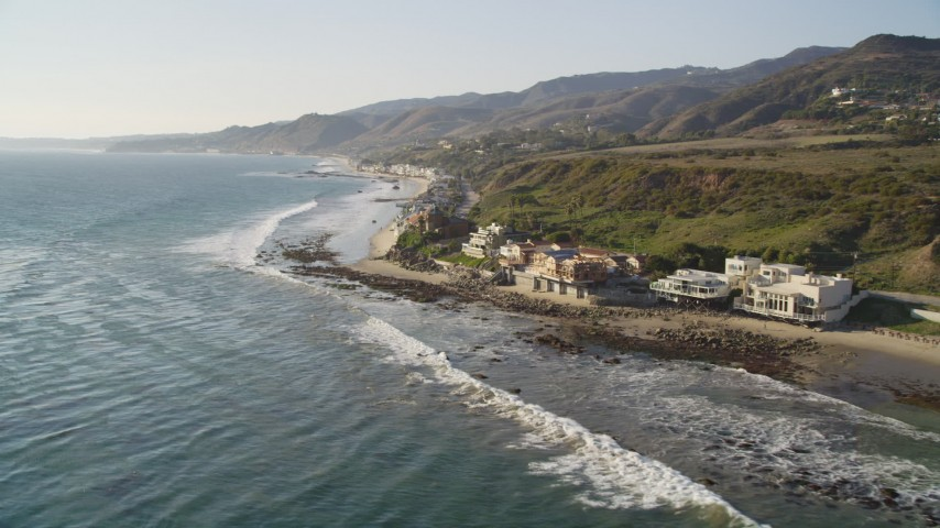 5K stock footage aerial video tilt from ocean waves to reveal oceanfront homes in Malibu, California Aerial Stock Footage | DCLA_155