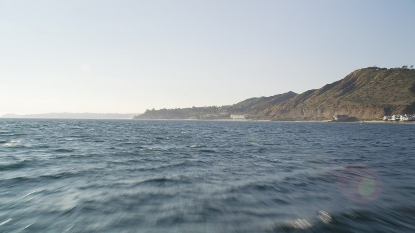 Tilt from the Blue Ocean to Reveal and Approach the Coast of Malibu Aerial Stock Footage | DCLA_160
