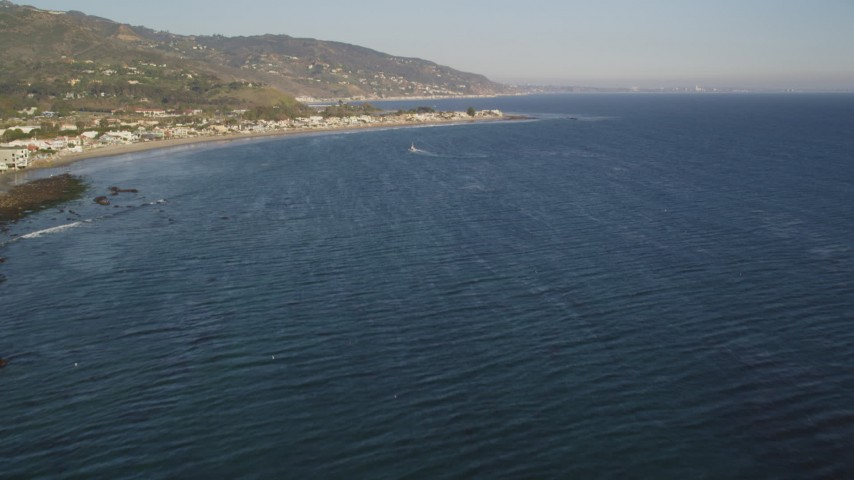5K stock footage aerial video fly over seagulls over the ocean and tilt to reveal Malibu, California Aerial Stock Footage | DCLA_170
