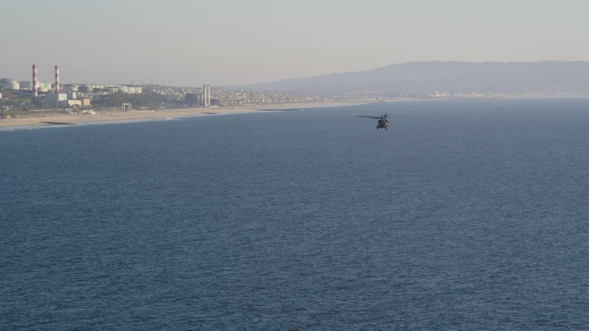 5K stock footage aerial video track military helicopter to reveal the coastline in El Segundo, California Aerial Stock Footage | DCLA_188