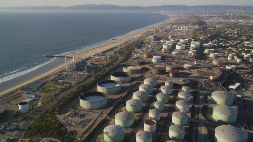 5K stock footage aerial video fly over oil tanks at refinery to approach beach in El Segundo, California Aerial Stock Footage | DCLA_195