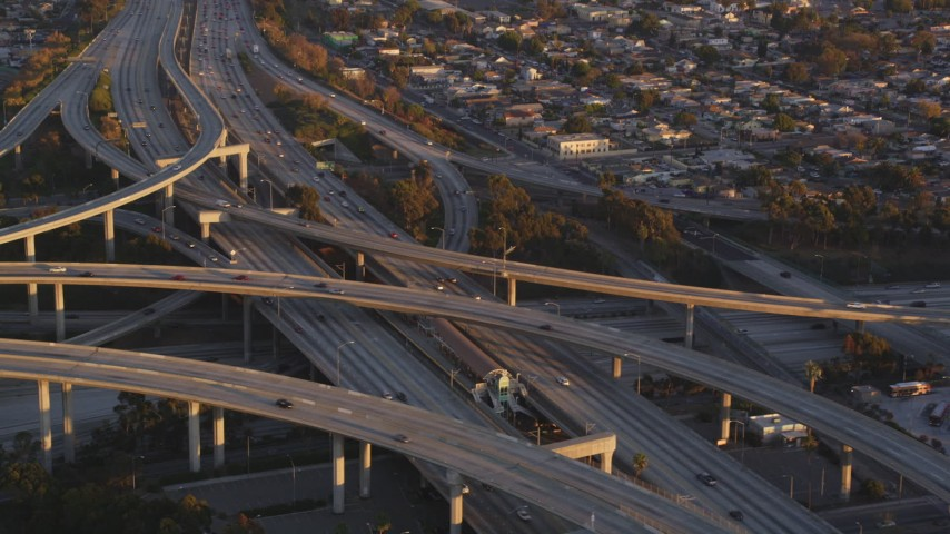 5K stock footage aerial video tilt to reveal light traffic on the 110/105 interchange in Westmont at sunset, California Aerial Stock Footage | DCLA_204