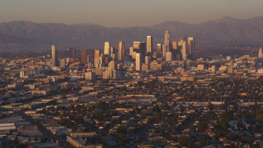 5K stock footage aerial video tilt from urban neighborhood to reveal Downtown Los Angeles skyline at sunset, California Aerial Stock Footage | DCLA_206