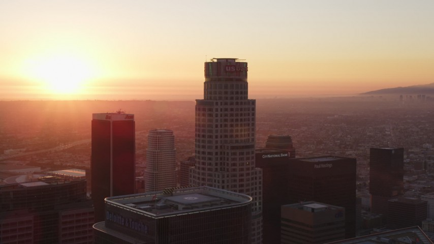 5K stock footage aerial video tilt from dark streets to reveal and approach Downtown Los Angeles towers at sunset, California Aerial Stock Footage | DCLA_233