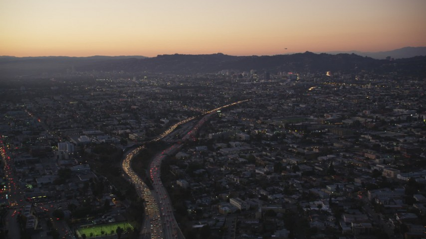 5K stock footage aerial video tilt from Highway 101 by Echo Park to reveal Hollywood at twilight, California Aerial Stock Footage | DCLA_269