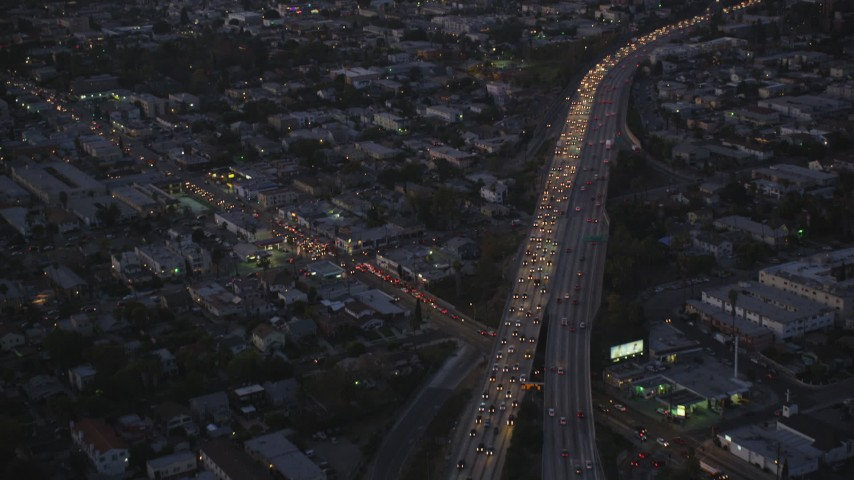 5K stock footage video tilt from bird's eye of Highway 101 to reveal Hollywood at twilight, California Aerial Stock Footage | DCLA_271