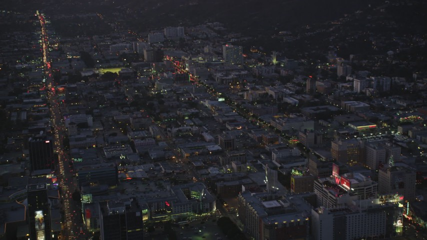 5K stock footage aerial video approach Hollywood with bright lights on city streets at twilight, California Aerial Stock Footage | DCLA_275