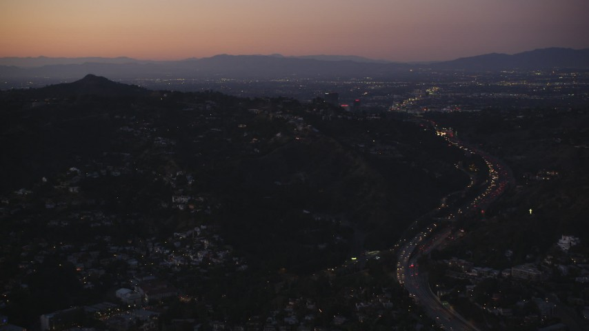 5K stock footage aerial video of Highway 101 through the Hollywood Hills near hillside homes at twilight, California Aerial Stock Footage | DCLA_276