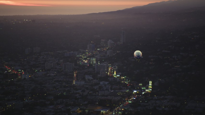 5K stock footage aerial video of flying by the back of a blimp flying over the Sunset Strip at twilight, West Hollywood, California Aerial Stock Footage | DCLA_277