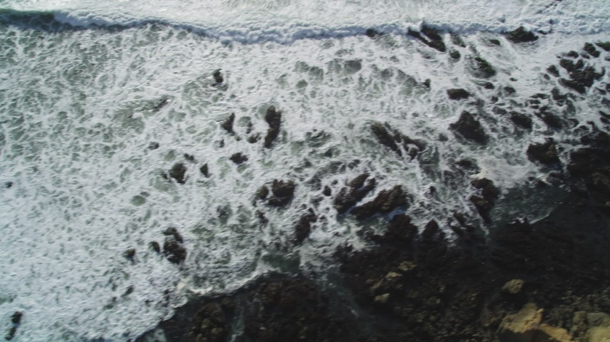 5K stock footage aerial video Bird's eye view of waves rolling into rocks on the coastline, Cambria, California Aerial Stock Footage | DCSF03_008