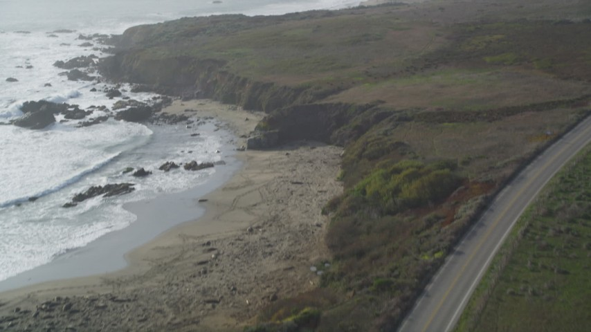 5K stock footage aerial video Tilt from Highway 1 to reveal Piedras Blancas Light Station, Point Piedras Blancas, California Aerial Stock Footage DCSF03_022 | Axiom Images