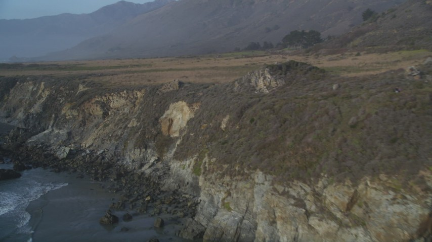 5K stock footage aerial video Fly by coastal cliffs and tilt to reveal ocean rocks, Big Sur, California Aerial Stock Footage | DCSF03_041