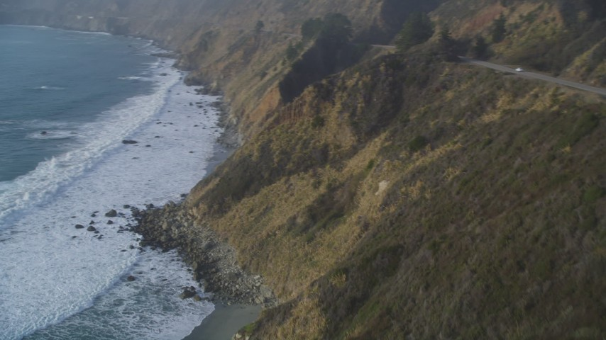 5K stock footage aerial video Pan to reveal waves rolling toward cliffs, Big Sur, California Aerial Stock Footage | DCSF03_045