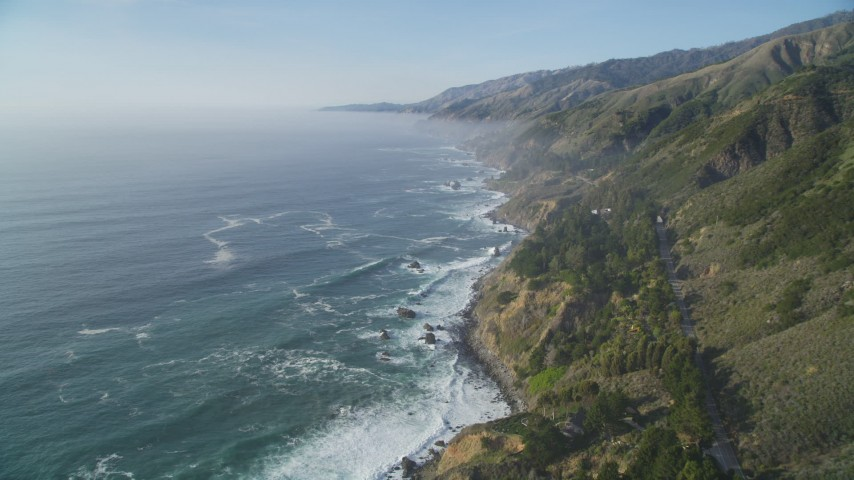 5K stock footage aerial video Fly over cliffs on the California coast with ocean waves rolling in, Big Sur, California Aerial Stock Footage | DCSF03_047