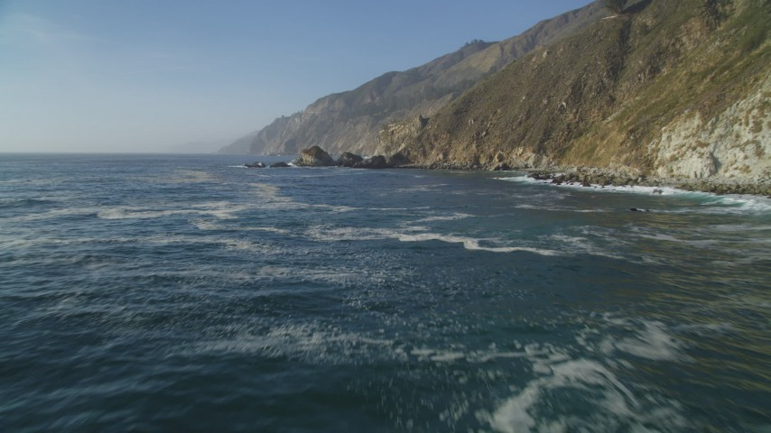 5K aerial video Flying low over the Pacific Ocean, pan to coastal cliffs, Big Sur, California Aerial Stock Footage | DCSF03_050